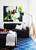 Coffee table, black sofa, patterned rug, modern artwork, standard lamps with wooden frame and black lampshade in living area