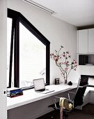 White, continuous desk and Eames chair below window with dark, sloping frame