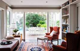 Living area with patterned, wing-back chair and Oriental rug in front of terrace doors