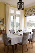 Christmas decorated dining table with upholstered chairs in the dining room with yellow tinted walls