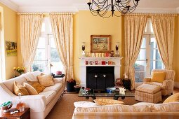 Upholstered set with coffee table and fireplace in the living room with French windows and yellow walls