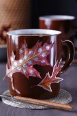 Colourful autumn leaves stuck on brown coffee mug