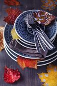 Stacked plates and painted autumn leaves