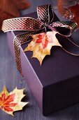 Gift box decorated with ribbon and autumn leaf pendant