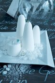 Arrangement of sugarloaves and small figurines on white plate