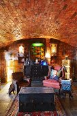 Dark wooden trunk in front of old leather armchairs in cellar-type room with brick barrel-vaulted ceiling