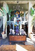 Stone heads in antique Greek style round religious statue on antique trunk in foyer with pillars and twin staircases