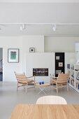 Wohnzimmer mit schlichten Designermöbeln im skandinavischen Stil und weißen Einbauten