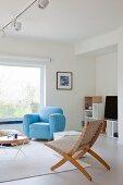 Hellblauer Polstersessel in skandinavischem Wohnflair mit reduzierter Möblierung