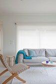 Hellgraues bequemes Polstersofa mit türkisfarbenem Plaid und Tabletttisch in hellen Wohnraum mit skandinavischem Charme