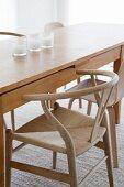 Langer Designer Holztisch mit Armlehnstuhl im skandinavischen Stil