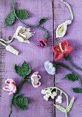 Crocheted flowers on purple wooden surface