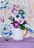 Purple, crocheted flowers in nostalgic milk jug arranged in front of floral wallpaper