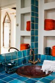 Blue tiled washstand with built in metal basin and vintage tap fittings in corner of bathroom