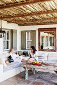 Two women chatting sitting on comfortable bench on roofed terrace with rustic coffee table on tiled floor