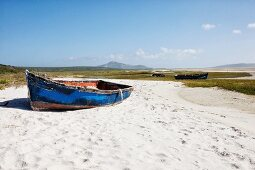 Simple boat with blue, peeling paint on sandy beach