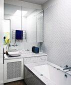Mirror cabinet over sink next to bathtub