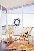Geschenke unter stilisiertem Weihnachtsbaum und Klassikerstuhl vor Fensterfront mit Dekokranz
