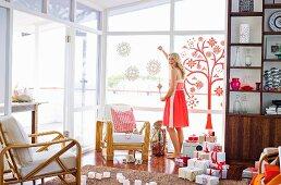 Wohnzimmer mit vielen Weihnachtsgeschenen, junge Frau beim Fensterdekorieren