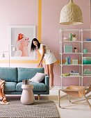 Sofa, open shelving and woman in front of pastel pink wall with yellow stripe