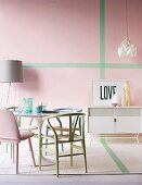 Various pastel chairs around Tulip Table and white sideboard in front of pink wall with green stripes
