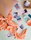 Postcards, beaker, and scarf arranged on pastel surface