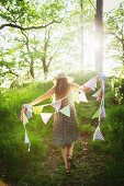 Young woman walking with bunting in forest