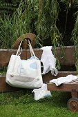 Hand-sewn beach bag with sailing boat motif and cord handles hanging on wooden fence