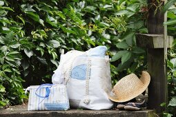 Hand-sewn beach bag and cosmetics bag next to straw hat on stone wall in garden