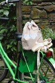 Hand-sewn, polka dot sports bag and ballet shoes on luggage rack of green-painted bicycle in garden