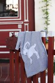 Grey T-shirt with hand-sewn animal motif hanging over wooden fence