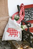 Cloth bag with appliqué, gingham animal motif hanging on garden bench
