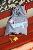 Cloth bag with hand-sewn, appliqué sausage dog motif and dog biscuits on garden bench