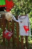 T-shirt & handbag with appliqué red stag motifs hanging on wooden fence