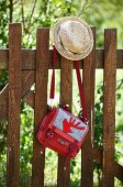 Straw hat & handbag with appliqué red stag motif hanging on wooden fence