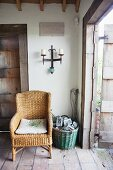 Wrought iron candle sconce above wicker chair next to basket on stone floor in rustic foyer with open front door