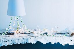 Festive dining table for wedding with garland of white carnations and candlelight below pendant lamp with white lampshade