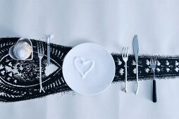 Love-heart of sugar sprinkles on white plate and cutlery with unusual handles next to pastry in heart-shaped dish on roll of wallpaper with black pattern