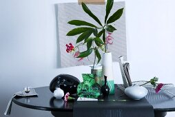 Florale Tischdeko mit aus Zeitungspapier ausgeschnittener Vasenform zwischen echten Porzellanvasen