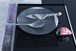 Mit Zeitungspapier umwickeltes Besteck auf Teller mit einem schwarzem Netz als puristische Tischdeko