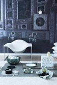 Tischdeko mit Zeitungspapier auf Teppich vor einem Designer Schalenstuhl; Fototapete mit Darstellung der Ahnengalerie in einem Barockschloss