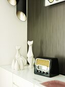 Fifties radio next to white ceramic vases and cat figurines on sideboard