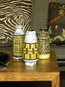 Collection of fifties-style vases painted back and yellow on oak coffee table