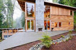 Gemauerter Kamin auf einer dreieckigen Terrasse vor modernem Holzhaus mitten im Wald