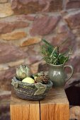 Artichokes in hand-crocheted felt basket on wooden stool against stone wall