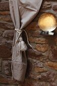 Curtain with felting wool tassel next to tealight and metal dish on bracket on stone wall