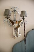 Sconce lamp with small fabric lampshades and painted angel figurine