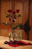 Red roses in retro glass bottles and Christmas pastry cutters on red cloth on wooden table