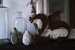 The number 25 in metal digits leaning on antique mirror next to glass demijohn bottles and Christmas decorations