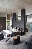Elegant, purist, designer bedroom with dark grey partition, view into ensuite bathroom with panoramic windows and continuous concrete ceiling